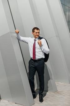 Jeune homme d'affaires rentrant du travail à la maison portant une veste sur l'épaule souriante posant près d'un immeuble de bureaux
