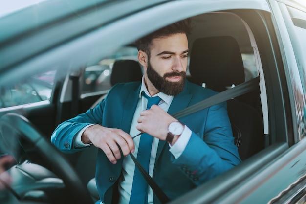 Jeune homme d'affaires responsable attrayant attacher la ceinture de sécurité tout en étant assis dans sa voiture chère.