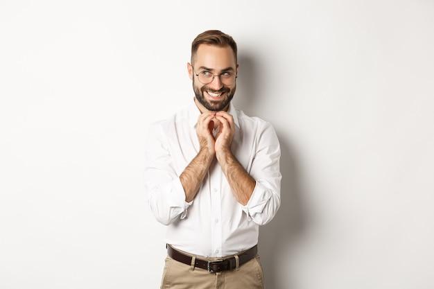 Jeune homme d'affaires rusé doigts de clocher et souriant sournois, plan intrigant, debout