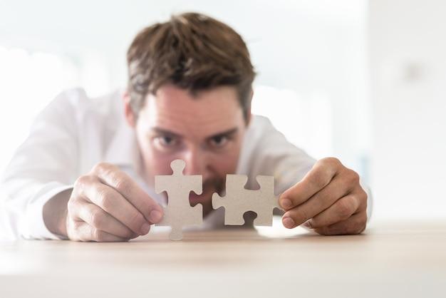 Jeune homme d'affaires s'appuyant sur son bureau joignant deux pièces de puzzle assorties.
