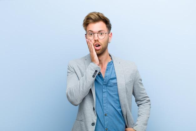 Jeune homme d'affaires se sentant choqué et étonné de se retrouver face à face avec incrédulité, bouche grande ouverte