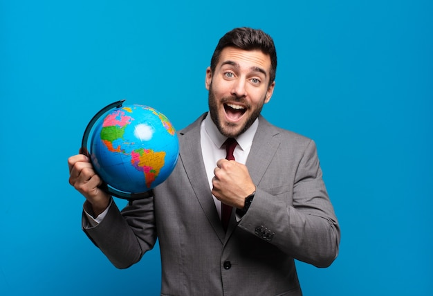 Jeune homme d'affaires se sentant heureux, positif et prospère, motivé face à un défi ou célébrant de bons résultats tenant une carte du globe terrestre