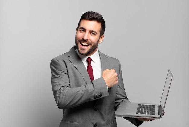 Jeune homme d'affaires se sentant heureux, positif et réussi, motivé face à un défi ou célébrant de bons résultats et tenant un ordinateur portable