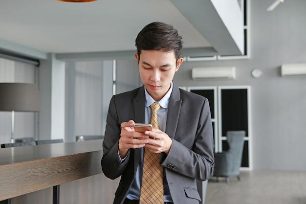 Jeune homme affaires, séance chaise, sur, lieu de travail, dans, bureau, utilisation, les, smartphone
