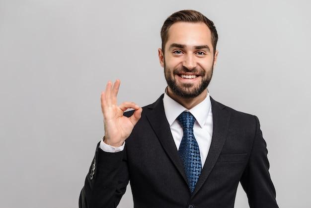 Jeune homme d'affaires séduisant portant un costume debout isolé sur un mur gris, geste ok