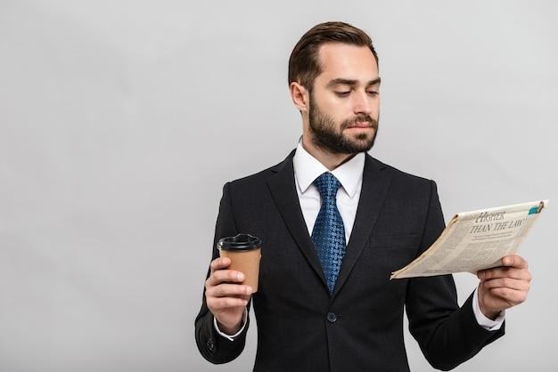 Jeune homme d'affaires séduisant portant un costume debout isolé sur un mur gris, lisant le journal tout en buvant du café à emporter