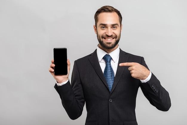 Jeune homme d'affaires séduisant portant un costume debout isolé sur un mur gris, montrant un téléphone portable à écran blanc, pointant