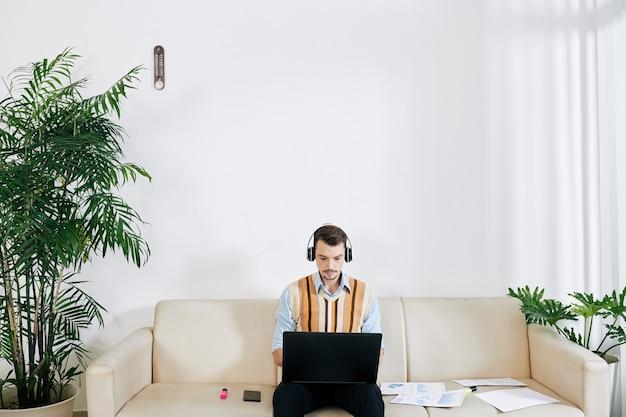 Jeune homme d'affaires sérieux dans les écouteurs assis sur un canapé dans le salon et travaillant sur un ordinateur portable