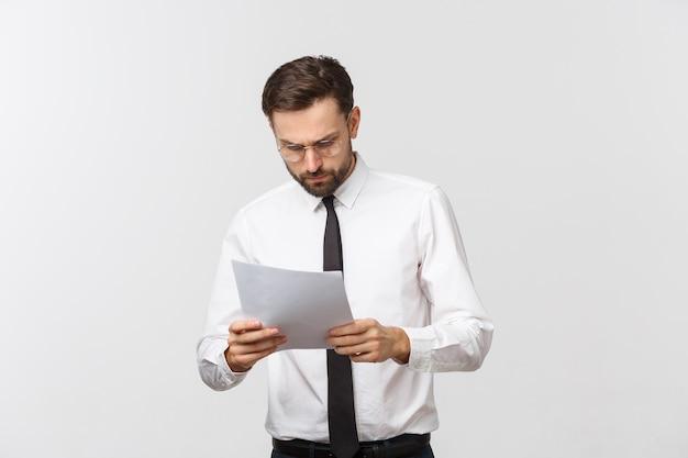 Jeune homme d'affaires sérieux écrit sur le presse-papiers, bel homme d'affaires porter élégant costume et cravate isolé sur espace blanc