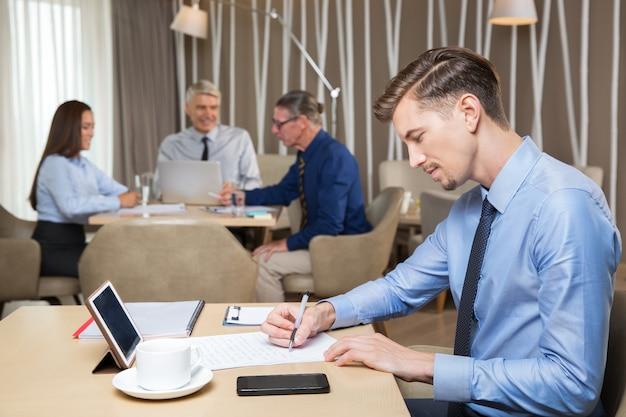 Jeune homme d'affaires sérieux et l'équipe de travail dans le café