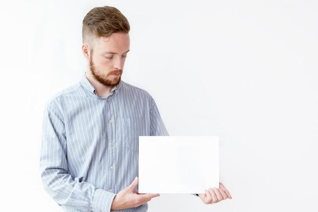 Jeune homme d'affaires sérieux montrant une affiche vierge