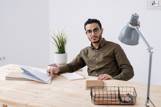 Jeune homme d'affaires sérieux en vêtements décontractés et lunettes assis par une table en bois au bureau tout en planifiant le travail et en vous regardant