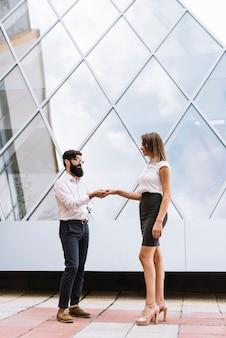 Jeune, homme affaires, serrer main, femme affaires, devant, bâtiment moderne