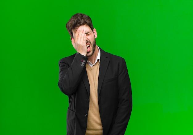 Jeune homme d'affaires somnolent, ennuyé et bâillant, avec un mal de tête et une main couvrant la moitié du visage contre le vert