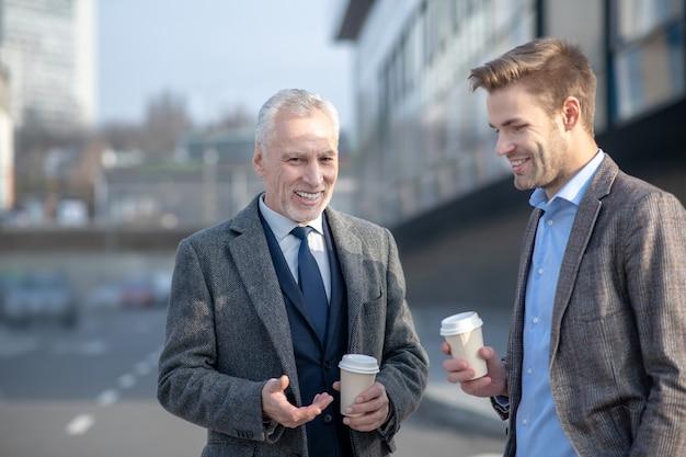 Jeune homme d'affaires et son mentor mature parlant dans la rue ayant une pause au travail