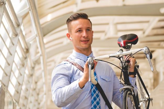 Jeune homme d'affaires avec son vélo.