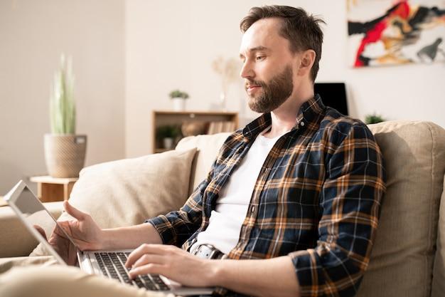 Jeune homme d'affaires songeur en tenue décontractée regardant l'écran de l'ordinateur portable en face de lui alors qu'il était assis sur un canapé à la maison