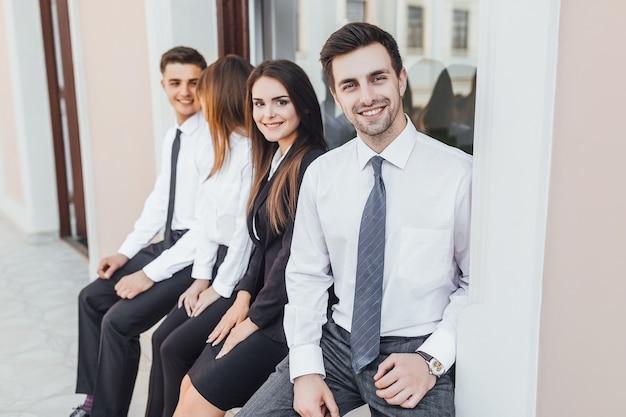 Jeune homme d'affaires souriant beau de race blanche et un collègue d'affaires dans la rue.