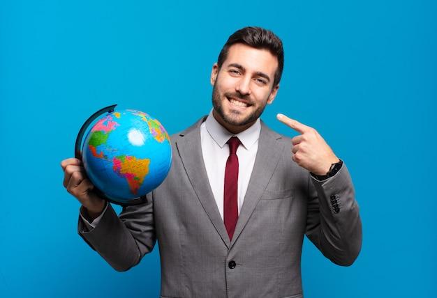Jeune homme d'affaires souriant avec confiance en montrant son large sourire, attitude positive, détendue et satisfaite tenant une carte du monde