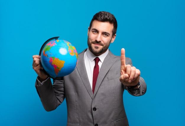 Jeune homme d'affaires souriant fièrement et avec confiance en faisant le numéro un pose triomphalement, se sentant comme un leader tenant une carte du globe terrestre