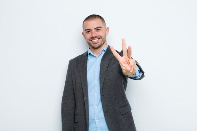 Jeune homme d'affaires souriant et regardant amical, montrant le numéro trois ou troisième avec la main vers l'avant, compte à rebours contre le mur plat