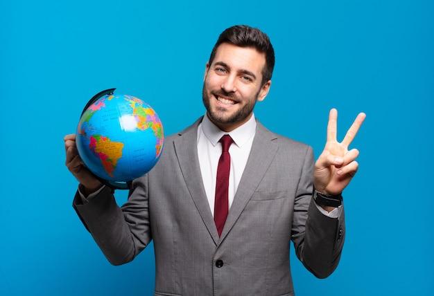 Jeune homme d'affaires souriant et regardant heureux, insouciant et positif, gesticulant la victoire ou la paix avec une main tenant une carte du globe terrestre