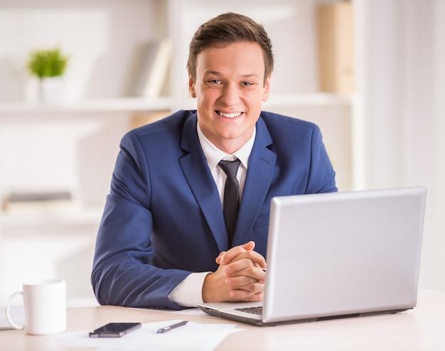 Jeune homme d'affaires souriant regarde la caméra.