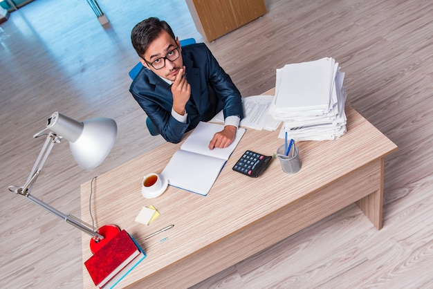 Jeune homme d'affaires stressé avec beaucoup de paperasse