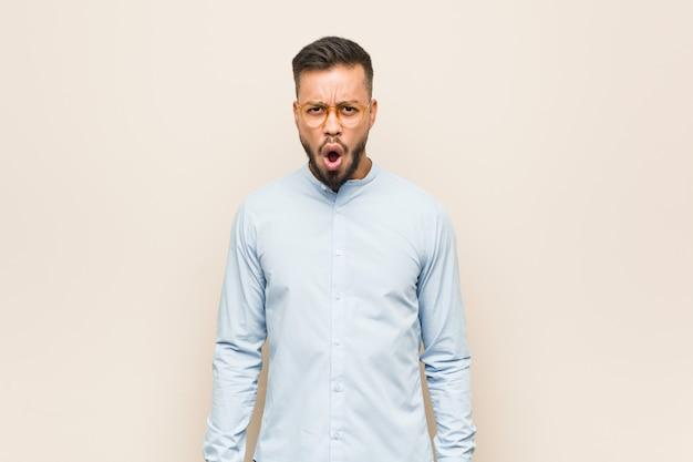Jeune homme d'affaires sud-asiatique hurlant de colère et d'agressivité.