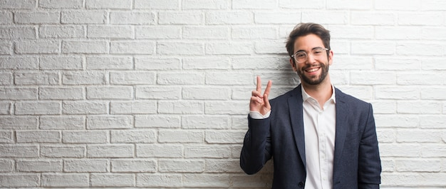 Jeune homme d'affaires sympathique amusant et heureux, positif et naturel, faisant un geste de victoire