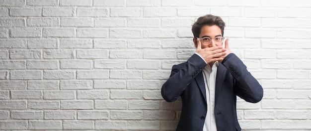 Jeune homme d'affaires sympathique couvrant la bouche, symbole du silence et de la répression