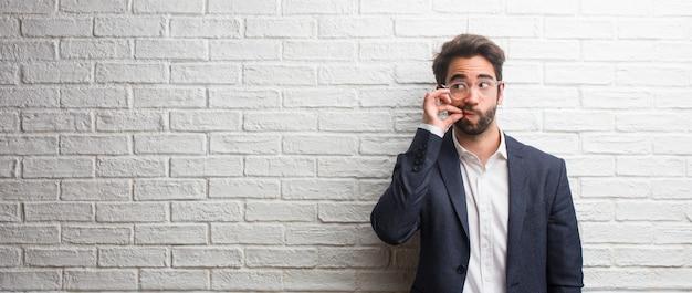 Jeune homme d'affaires sympathique gardant un secret ou demandant le silence, visage sérieux