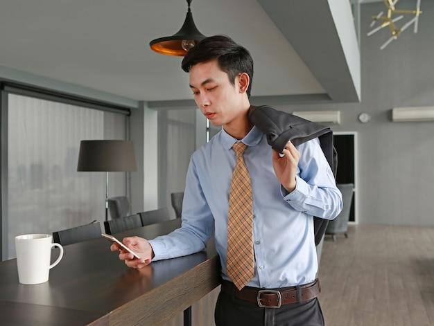 Jeune homme affaires, table, utilisation, smartphone