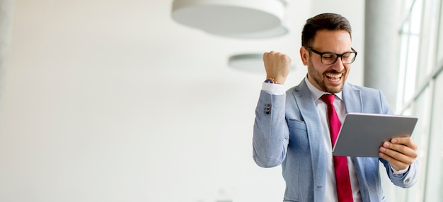 Jeune homme d'affaires avec tablette numérique au bureau