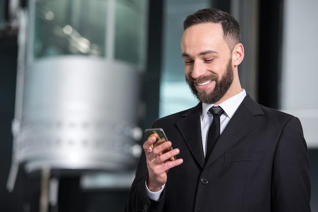 Jeune homme d'affaires avec téléphone portable au bureau moderne.