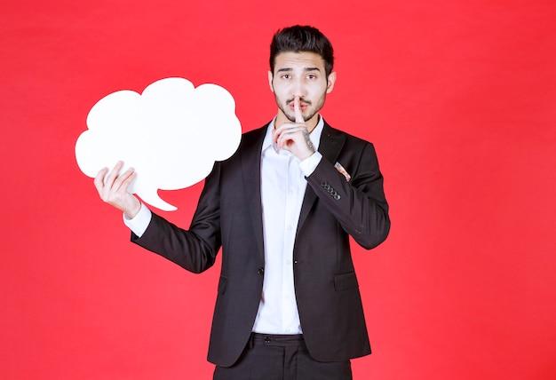 Jeune homme d'affaires tenant une bulle de dialogue vide pour la publicité