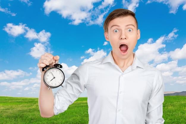 Jeune homme d'affaires tenant une horloge