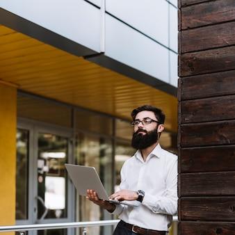 Jeune, homme affaires, tenant ordinateur portable, dans main, regarder loin