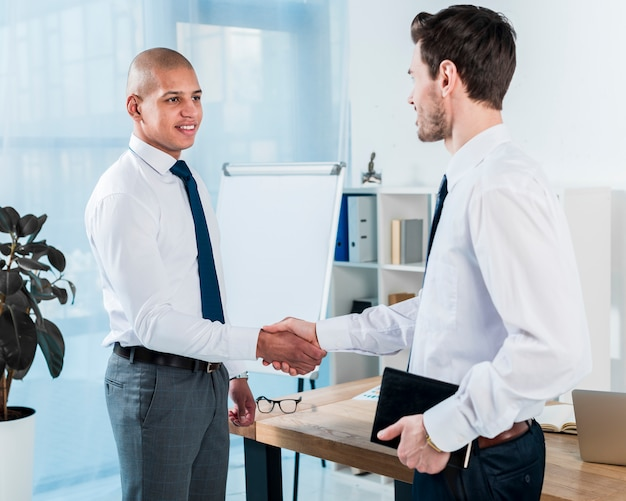 Jeune homme d'affaires tenant son journal dans la main se serrant la main avec son collègue