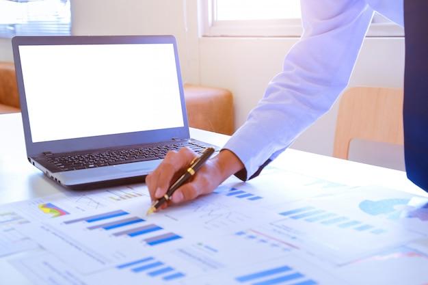 Jeune homme d'affaires tenant un stylo pointant vers le graphique et graphique au bureau.