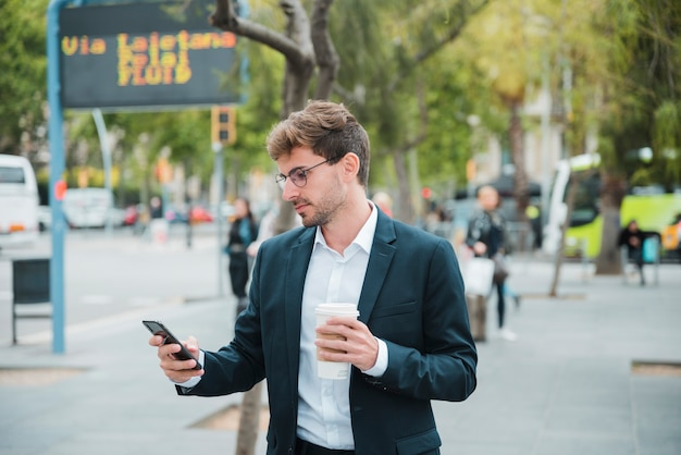 Jeune homme d'affaires tenant une tasse de café jetable en regardant téléphone mobile