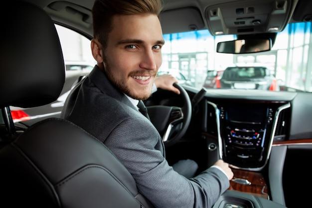 Jeune homme d'affaires teste une nouvelle voiture.