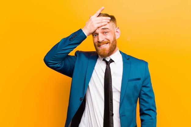 Jeune homme d'affaires à la tête rouge paniqué devant une échéance oubliée, se sentant stressé, devant cacher un gâchis ou une erreur