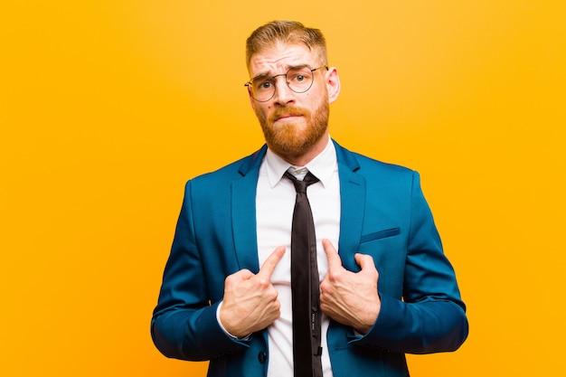 Jeune homme d'affaires tête rouge pointant sur soi avec un regard confus et interrogatif, choqué et surpris d'être choisi mur orange