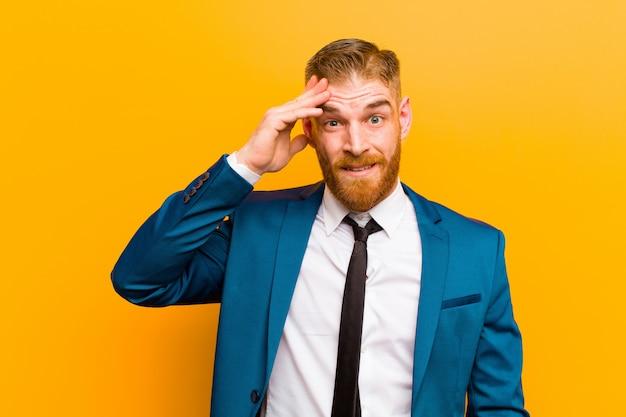 Jeune homme d'affaires à la tête rouge à la recherche de bonheur étonné et surpris souriant et réalisant des bonnes nouvelles incroyables et incroyables sur fond orange