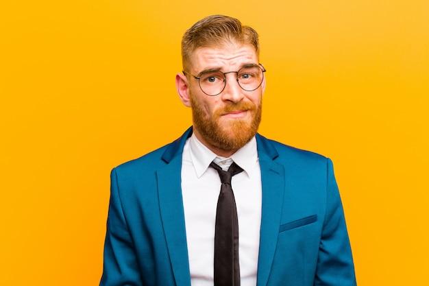 Jeune homme d'affaires à la tête rouge à la recherche perplexe et confuse, se mordant la lèvre avec un geste nerveux, ne connaissant pas la réponse au mur orange problématique