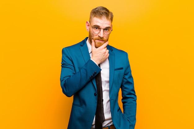 Jeune homme d'affaires à la tête rouge à la recherche de sérieux, confus, incertain et réfléchi, doutant des options ou des choix contre orange