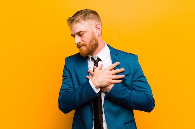 Jeune homme d'affaires à la tête rouge regardant triste, blessé et le coeur brisé, tenant les deux mains près du cœur, pleurant et se sentant déprimé