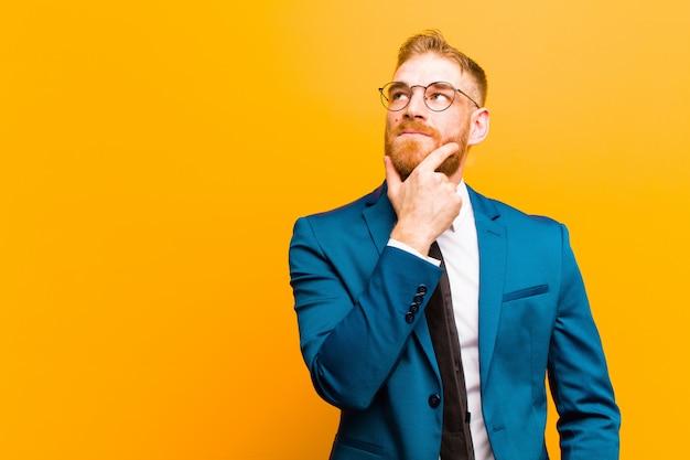 Jeune homme d'affaires à tête rouge se sentant pensif, se demandant ou imaginant des idées, rêvassant et levant les yeux pour copier l'espace