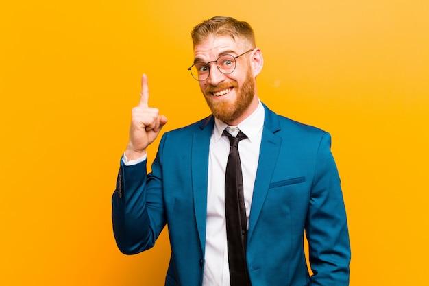 Jeune homme d'affaires à la tête rouge se sentir comme un génie heureux et excité après avoir réalisé une idée, levant gaiement le doigt, eureka!